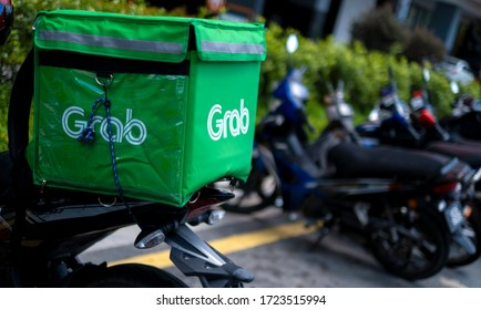 KUALA LUMPUR, MALAYSIA - MAY 05, 2020: Food delivery service rider using motorcycle for GrabFood. Food delivery service through online mobile application.