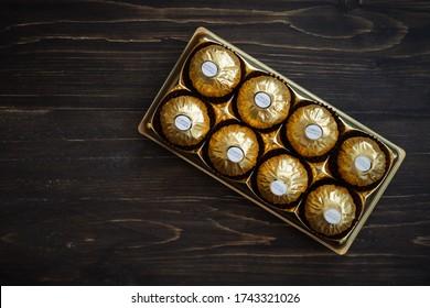 Kuala Lumpur, Malaysia - May 16, 2020: Ferrero Rocher premium chocolate sweets on wooden background. Luxury taste.