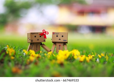Kuala Lumpur, Malaysia – May 20, 2017 : A lovely couple of Danbo playing in the garden with a green bokeh. Image has grain or blurry or noise and soft focus when view at full resolution.
