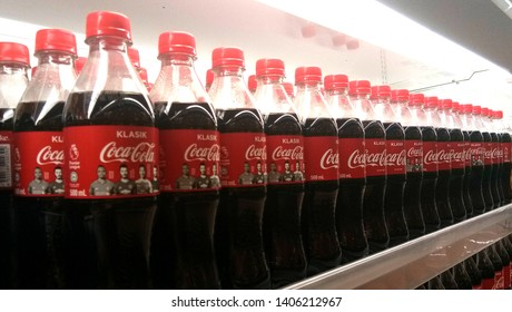 KUALA LUMPUR, MALAYSIA- MAY 23, 2019: Coke in bottles on row of shelf display for sale in hypermarket grocery store. Coca-Cola, or Coke, is a carbonated soft drink produced by The Coca-Cola Company.