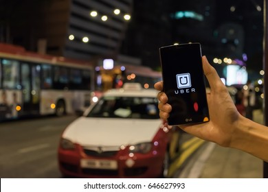Kuala Lumpur Malaysia - MAY 24,2017 : A man hand holding Uber app showing on LG G4 on road and red car, Uber is smart phone app-based transportation network.
