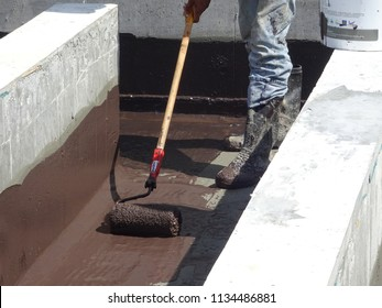 KUALA LUMPUR, MALAYSIA -MAY 25, 2018: Waterproofing layer applied by construction workers on top of concrete slab. Waterproofing layer to prevent water from entering below of the concrete slab.