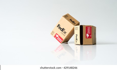 """Kuala Lumpur, Malaysia - May 26, 2016: FedEx shipping box on empty background. FedEx Corporation is global courier delivery services company. """"FedEx"""" is a syllabic abbreviation of Federal Express"""