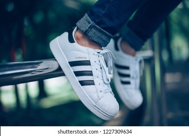 Kuala Lumpur, Malaysia - Nov 2018 : A girl wearing Adidas Superstar white with black stripes shoes on street environment as background.