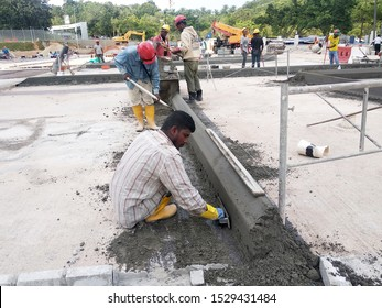 KUALA LUMPUR, MALAYSIA -NOVEMBER 02, 2018: Construction workers fabricating concrete road kerb at the construction site. They are using the in-situ method using the standard metal mold.