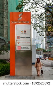 "Kuala Lumpur, Malaysia - November 14 2014: Signage at Sunway Tower, including the companies ""Worley Parsons"", ""San Francisco Coffee"", ""ACCA"" and ""Ranhill"". A muslima with hijab  is passing by."