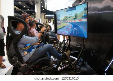 KUALA LUMPUR, MALAYSIA -NOVEMBER 23, 2017: People playing with race car simulation game. Displayed with big screen monitors complete with cockpit controls like a real racing car.