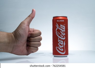 Kuala Lumpur, Malaysia - November 25, 2017 : Photo Of Cold Coca-Cola Classic (KLASIK) Malaysia Edition with micro dew and hand On White Background. Coca-Cola Company Is The Most Popular on Market