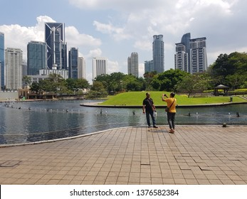 Kuala Lumpur, Malaysia. November 26, 2018. Tourists taking photo at Symphony Lake, KLCC Park, one of major tourist attraction in Malaysia's capital, with Kuala Lumpur's skyscapers on background