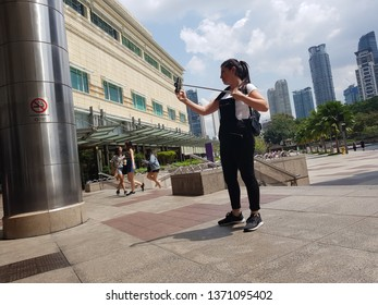 Kuala Lumpur, Malaysia. November 27, 2018. A girl taking selfie at Promenade in front of the Suria KLCC, one of major shopping mall and tourist attraction in Malaysia's capital