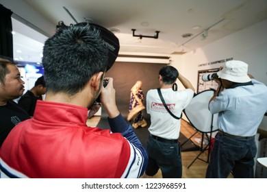 Kuala Lumpur, Malaysia – November 3, 2018: Group of photographers learning creative portrait during photo shooting in photography studio.