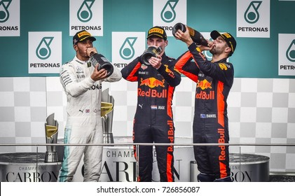 KUALA LUMPUR, MALAYSIA - OCTOBER 01, 2017 : Race winner Max Verstappen with Lewis Hamilton and Daniel Ricciardo celebrate on the podium during Malaysia Grand Prix at Sepang Circuit