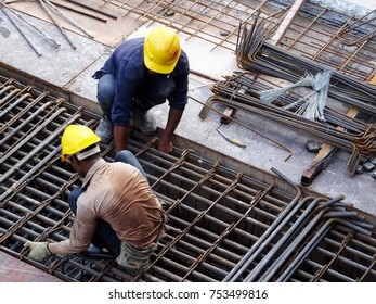 KUALA LUMPUR, MALAYSIA -OCTOBER 16, 2017: Construction workers fabricating steel reinforcement bar at the construction site. The reinforcement bar was tied together using tiny wires