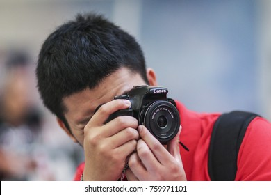 KUALA LUMPUR, MALAYSIA - OCTOBER 17, 2015. A Chinese man using his Canon camera to taking picture at the mall in Kuala Lumpur.