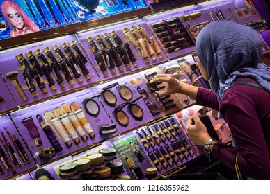 Kuala Lumpur, Malaysia - October 18, 2018 : Muslim hijab lady testing and buying cosmetics in a beauty store.