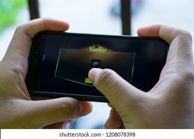 KUALA LUMPUR, MALAYSIA, OCTOBER 20 2018 : Selective focus hand holding a smartphone with Player's Unknown Battleground also known as PUBG online shooting gaming