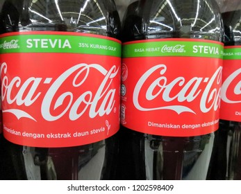 Kuala Lumpur, Malaysia - October 2018:  Closeup Coke in bottles on row of shelf display for sale in supermarket. Coca-Cola, or Coke is a carbonated soft drink manufactured by The Coca-Cola Company.