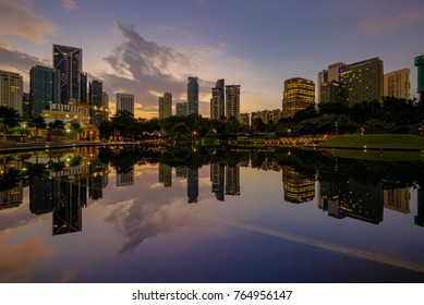 Kuala Lumpur, MALAYSIA - October 7, 2017: Reflection of buildings over calm Symphony lake of KLCC Park during sunrise