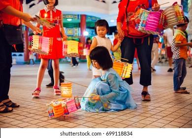 Kuala Lumpur, Malaysia - September 15, 2016:  Little girl plays with paper lanterns at Thean Hou Temple at the lantern parade during Mid-Autumn Festival on September 15, 2016,  Kuala Lumpur, Malaysia.
