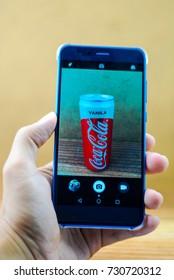 KUALA LUMPUR, MALAYSIA - SEPTEMBER 15, 2017 : A man capture an aluminium can of Coca cola vanilla soft drink using smart phone.The Coca-Cola Company, an American