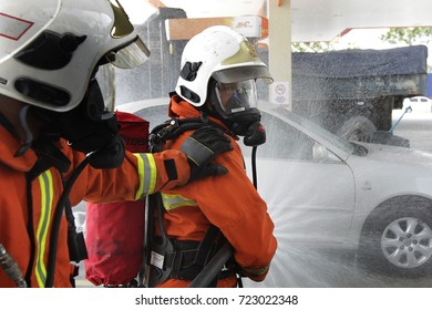 KUALA LUMPUR, MALAYSIA - SEPTEMBER 27, 2017. Malaysian firefighters spraying water to the car as they participates in safety simulation in Kuala Lumpur.