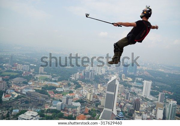KUALA LUMPUR, MALAYSIA - SEPTEMBER 27: A BASE jumpers in jumps off from KL Tower at September 27, 2014. Their are an experienced BASE jumpers from all around the world.