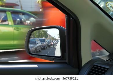 Kuala Lumpur, Malaysia-08/13/2016: The side rear mirror of a car in a traffic jam