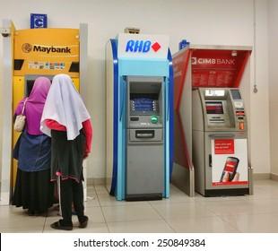 KUALA LUMPUR, MALAYSIA-JUNE 22, 2014: Unidentified people withdraw money from ATM machines in Kuala Lumpur. Maybank, RHB Bank and CIMB Bank are three top banks in Malaysia.