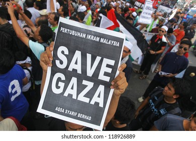 """KUALA LUMPUR, MALAYSIA-NOV 16: A man holds a poster """"SAVE GAZA"""" infront of US Embassy in Kuala Lumpur, Malaysia on November 16. 2012. Israeli assault on Gaza has spread outrage over muslims country."""