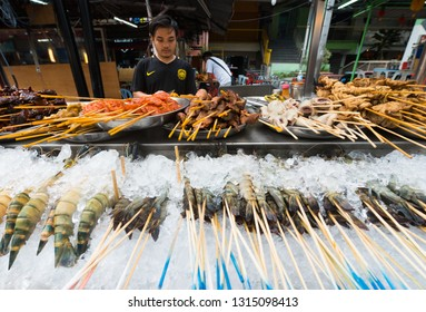 KUALA LUMPUR - MARCH 13, 2017: An unidentified man sells assorted grilled food on skewers in Jalan Alor Street famous with budget restaurants of various cuisines of the world.