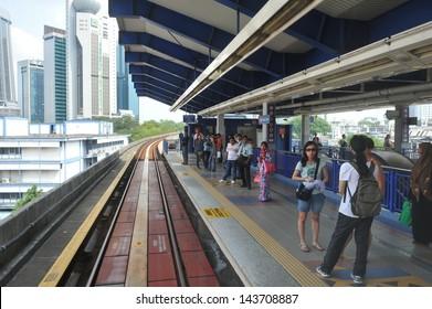 KUALA LUMPUR - MAY 14: Passengers wait on a train station platform of the RapidKL LRT  rail network on May 14, 2013 in Kuala Lumpur, Malaysia. RapidKL transports approximately 690,000 people daily.