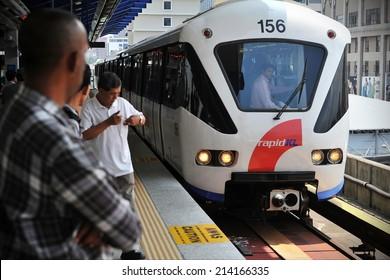 KUALA LUMPUR - MAY 14: A RapidKL LRT train pulls into a city centre station on May 14, 2013 in Kuala Lumpur, Malaysia. RapidKL's transport network serves approximately 690,000 passengers daily.