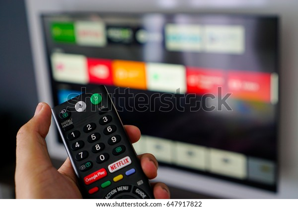 Kuala Lumpur - May 27th 2017 : Android TV home-user are using Google Voice Search (OK Google) function on Sony Remote by speaking to search for media, movie, music or any content on Internet.