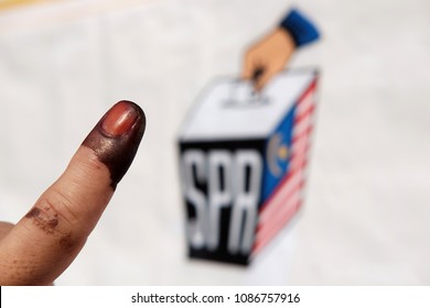 KUALA LUMPUR - MAY 9, 2018: A finger with indelible ink against a blur background of the Election Commission banner in KL. The EC is an independent body overseeing Malaysia 14th general election.