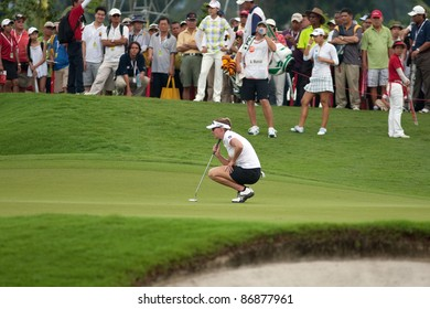 KUALA LUMPUR- OCTOBER 16: Brittany Lang of the USA checks the green of the 18th hole at the KL Golf & Country Club at the Sime Darby LPGA 2011 tournament on October 16, 2011 in Kuala Lumpur, Malaysia.