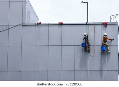 Kuala Lumpur, October 2, 2017- Group of workers cleaning building wall on high rise building near Malaysia International Trade & Exhibition Centre, Kuala Lumpur, Malaysia.