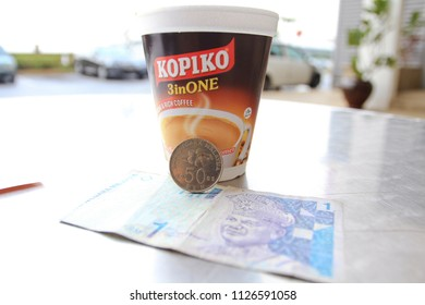 KUALA LUMPUR OCTOBER 2011 - The cashier is placing a cup of hot kopiko coffee on the metal table during breakfast time
