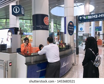 KUALA LUMPUR - SEPT 11, 2017: An unidentified man tourist asks at the information counter in the departure area of the Kuala Lumpur Airport. It is one of the major airports in South East Asia