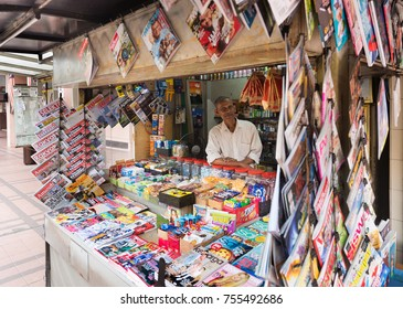 KUALA LUMPUR - SEPT 12, 2017: An unidentified man sells newspapers and magazines at a newsstand near Petaling Street known as Chinatown