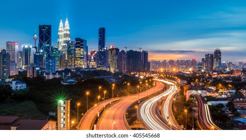 Kuala Lumpur skyline with traffic car light on highway leading line to Twin towers during twilight at Kuala Lumpur Malaysia