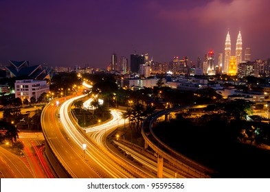 Kuala Lumpur twin towers with stunning light trail from the busy highway traffic.
