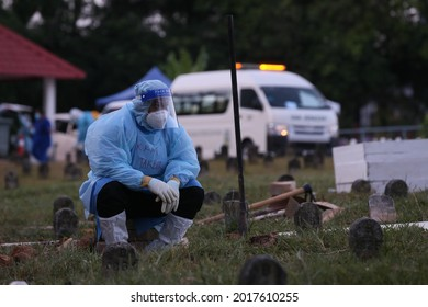 Kuala Lumpur,1 August 2021-Malaysia.Malaysia health workers wearing full personal protective equipment are seen tiredly after covid 19 body funeral service.