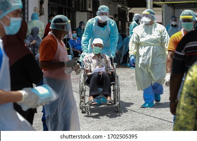 Kuala Lumpur,11 April 2020-Malaysia.A medical worker helps an old man on a wheel chair after screening covid 19 test in Kuala Lumpur while wearing personal protective equipment suit.