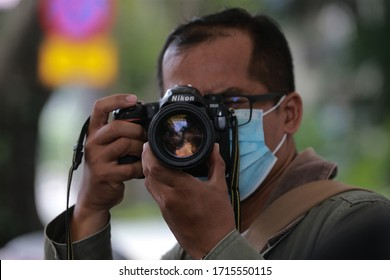 Kuala Lumpur,27 April 2020-Malaysia.A photojournalist point a camera lens while wearing a face mask to cover  covid 19 pandemic in Kuala Lumpur. (selective focus photography)
