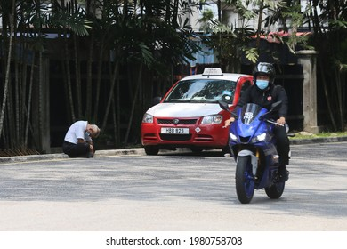 Kuala Lumpur,27 May 2021-Malaysia. An old taxi drive fell a sleep outside his taxi while waiting for a passenger during movement control order in Malaysia.