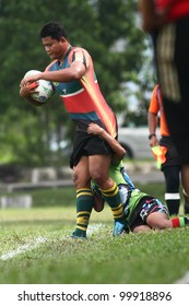 KUALA LUMPUR-APRIL 8: Keris Conlay player hold-on to an unidentified ATM RAMD player during a Malaysian Rugby Union (MRU) Super League match on April 8, 2012 in Kuala Lumpur, Malaysia.Conlay won 29-12
