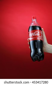 Kuala Lumpur,Malaysia 11th July 2016, Hand hold a bottle 1.5 litre Coca-Cola on red background. Coca Cola drinks are produced and manufactured by The Coca-Cola Company.