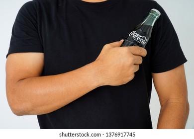 Kuala Lumpur,Malaysia 22 April 2019,Photo of a hand holding glass bottle of Coca Cola.