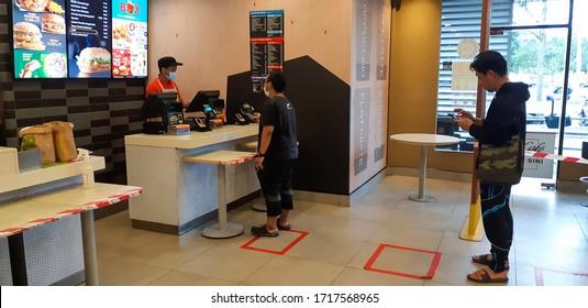 KUALA LUMPUR,MALAYSIA - APRIL 28,2020: People apply social distancing during covid 19 crisis to buy food at McDonald restaurant.