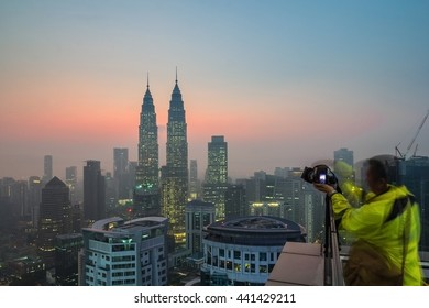 KUALA LUMPUR,MALAYSIA- JANUARY 13 2016:Kuala lumpur city under hazy days with a photographer takes picture.The image looks blur and soft due to long exposure and hazy day